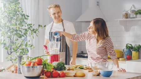 Handsome Young Man in Glasses Wearing Apron and Beautiful Girl are Making A Smoothie in the Kitchen. Happy Couple are Preparing Healthy Organic Beverage. Male and Female at Home on a Sunny Day.