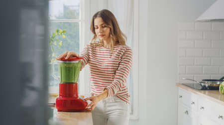 Beautiful Young Female Preparing a Healthy Green Smoothie in a Blender. Authentic Stylish Kitchen with Healthy Vegetables. Natural Clean Products from Organic Farming Used to Make Drinks. Banco de Imagens