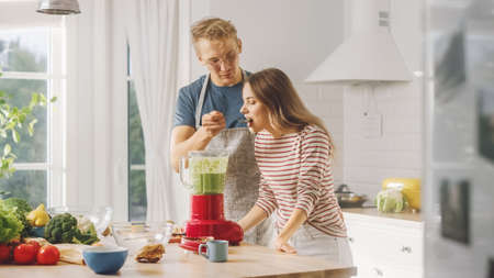 Handsome Young Man in Glasses Wearing Apron and Beautiful Girl are Making A Smoothie in the Kitchen. Happy Couple are Trying Healthy Organic Beverage. Male and Female at Home on a Sunny Day.