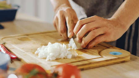 Close Up Shot of a Man Chopping an Onion with a Sharp Kitchen Knife. Preparing a Healthy Organic Meal in a Modern Kitchen. Natural Clean Diet and Healthy Way of Life Concept.