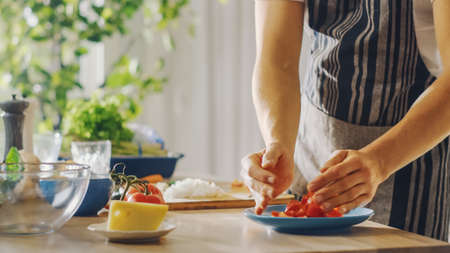 Close Up Shot of a Man Putting a Chopped Tomato in a Bowl. Preparing a Healthy Vegetarian Organic Salad Meal in a Modern Kitchen. Natural Clean Diet and Healthy Way of Life Concept.