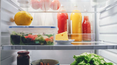 Point of View POV Shot from Kitchen Fridge. Refrigerator Lit and Full of Good Food: Cherry Tomatoes, Cheese, Fresh Juices and Cabbage, Made Salad, Lemon.
