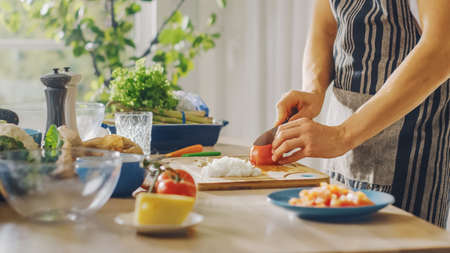 Close Up Shot of a Man Chopping a Tomato with a Sharp Kitchen Knife. Preparing a Healthy Organic Salad Meal in a Modern Kitchen. Natural Clean Diet and Healthy Way of Life Concept.