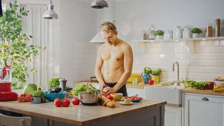 Handsome Shirtless Man Chopping a Carrot with a Sharp Kitchen Knife. Preparing a Healthy Organic Salad Meal in a Modern Kitchen. Topless Male on Diet.