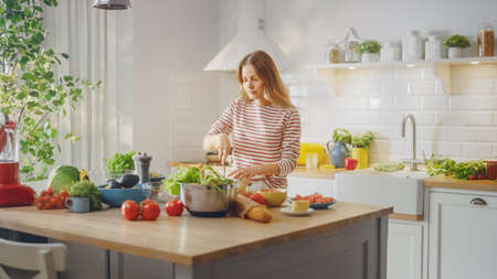 Young Female in Striped Jumper is Making a Healthy Organic Salad in a Modern Sunny Kitchen. Authentic Woman is Chopping a Cauliflower with a Knife. Natural Clean Diet and Healthy Way of Life Concept. Banco de Imagens