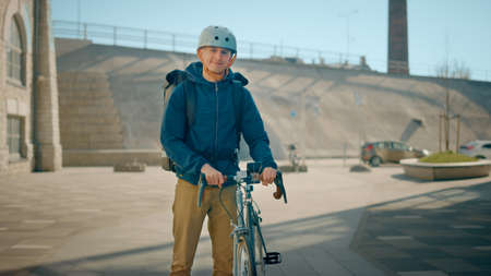 Handsome Happy Food Delivery Man Wearing Thermal Backpack and Safety Helmet Stands Beside his Bike in the Stylish Modern City District. Portrait of the Smiling Courier Delivering Restaurant Order