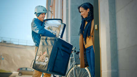 Happy Food Delivery Man Wearing Thermal Backpack on a Bike Delivers Restaurant Order to a Female Customer. Courier Delivers Takeaway Lunch to a Girl in Modern City District Office Building. Low Angle