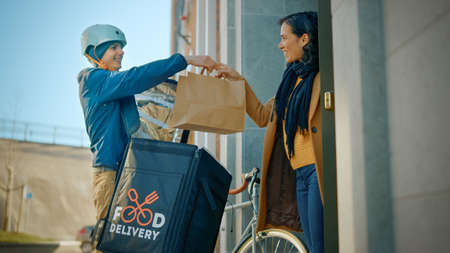 Happy Food Delivery Man Wearing Thermal Backpack on a Bike Delivers Restaurant Order to a Beautiful Female Customer. Courier Delivers Takeaway Lunch to Gorgeous Girl in Office Building. Low Angle