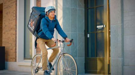 Handsome Happy Food Delivery Man Wearing Thermal Backpack Rides his Bike Through the Stylish Modern City District. Shot of Smiling Courier Delivering Restaurant Order Safely. Reklamní fotografie