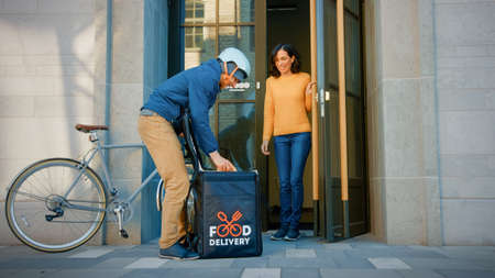 Happy Food Delivery Man Wearing Thermal Backpack on a Bike Delivers Restaurant Order to a Happy Female Customer. Courier Delivers Takeaway Lunch to Office Building.