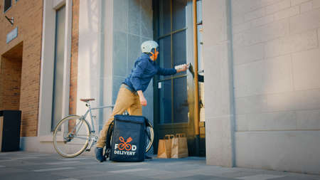 Food Delivery Man Wearing Thermal Backpack on Bike Delivers Restaurant Order, Leaving it Under the Door. Concept: Contactless No Contact Delivery for Social Distancing, Self Isolation