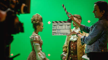On Big Film Studio Professional Crew Shooting Period Costume Drama Movie. On Set: Camera Assistant Using Clapperboard, Cameraman Shooting Green Screen Scene with Two Actors in Renaissance Clothes Stock Photo