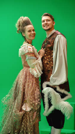 On Big Film Studio Two Talented Actors of Female and Male Playing a Beautiful Lovely Couple Wearing Renaissance Clothes and Smiling on Camera. The Scene on Green Screen.