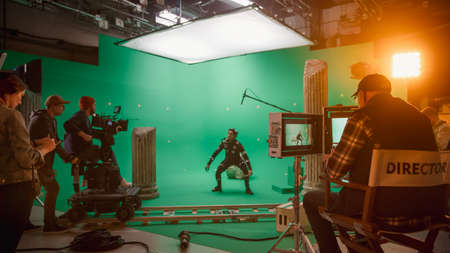 In the Big Film Studio Professional Crew Shooting Blockbuster Movie. Director Commands Cameraman to Start shooting Green Screen CGI Scene with Actor Wearing Motion Capture Suit and Head Rig Zdjęcie Seryjne