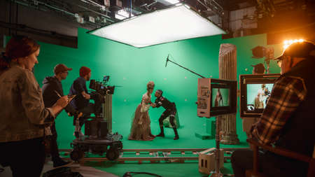 On Big Film Studio Professional Crew Shooting History Costume Drama Movie. On Set: Directing Green Screen Scene with Beautiful Lady Wearing Renaissance Costume Meets Actor Playing Monster