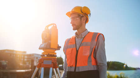 Construction Worker Using Theodolite Surveying Optical Instrument for Measuring Angles in Horizontal and Vertical Planes on Construction Site. Worker in Hard Hat Making Projections for the Building.
