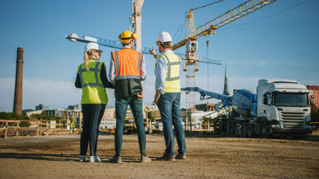 Diverse Team of Specialists Stand with Their Backs on Construction Site. Real Estate Building Project with Civil Engineer, Architect, Business Investor Discussing Planning and Development Details.