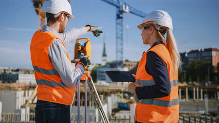 Construction Worker Using Theodolite Surveying Optical Instrument for Measuring Angles in Horizontal and Vertical Planes on Construction Site. Engineer and Architect Using Tablet Next to Surveyor.
