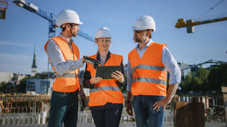 Diverse Team of Specialists Use Tablet Computer on Construction Site. Real Estate Building Project with Civil Engineer, Architect, Business Investor Discussing Planning and Development Details.