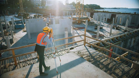 Construction Worker Using Theodolite Surveying Optical Instrument for Measuring Angles in Horizontal and Vertical Planes on Construction Site. Worker in Hard Hat Making Projections for the Building. Stockfoto
