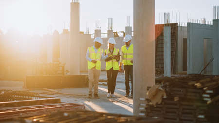 Diverse Team of Specialists Taking a Walk Through Construction Site. Real Estate Building Project with Senior Civil Engineer, Architect, General Worker Discussing Planning and Development Details. Standard-Bild