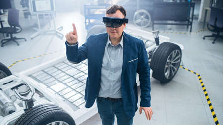 Automotive Engineer Using Augmented Reality Headset Making Touching Gestures. In Innovation Laboratory Facility Concept Vehicle Frame Includes Wheels, Suspension, Engine and Battery.