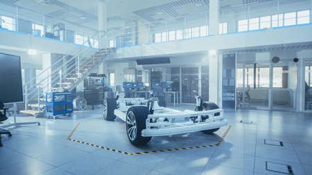 Concept of Authentic Electric Car Platform Chassis Prototype Standing in High Tech Industrial Machinery Design Laboratory. Hybrid Frame include Tires, Suspension, Engine and Battery. Banque d'images