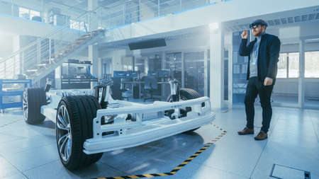 Automotive Engineer Working on Electric Car Chassis Platform, Using Augmented Reality Headset. In Innovation Laboratory Facility Concept Vehicle Frame Includes Wheels, Suspension, Engine and Battery. Banque d'images