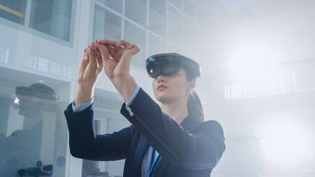 Female Engineer Using Augmented Reality Headset Making Gestures of working with Virtual Objects in the Air. In Innovation High Tech Laboratory Facility with Futuristic Atmosphere. Foto de archivo