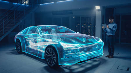 Automotive Engineer Working on Electric Car Chassis Platform, Using Tablet Computer with Augmented Reality 3D Software. Futuristic Atomative Facility: Virtual Design with Mixed Technology Application.