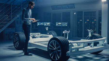 Automobile Engineer Working on Electric Car Platform Chassis Prototype, Using Tablet Computer with 3D CAD Software Modelling. Innovative Facility: Vehicle Frame with Wheels, Engine,Battery and
