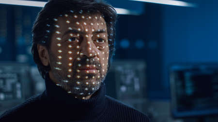 Biometric Facial Recognition Scanning Proccess. Man Getting Identified by Hardware Scanning Facial Feautures with Light. Futuristic Concept Shot in High Tech Laboratory