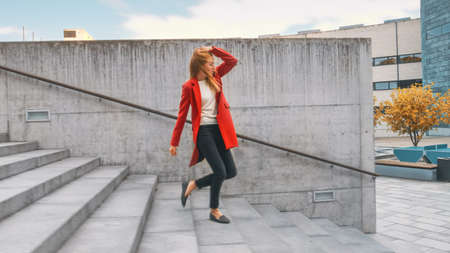 Cheerful and Happy Young Woman Actively Dancing While Walking Down the Stairs. Shes Wearing a Long Red Coat. Scene Shot in an Urban Concrete Park Next to Business Center. Day is Bright.