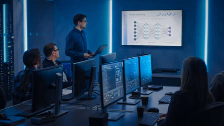 Team of Professional IT Developers Have a Meeting, Speaker Talks about New Blockchain Based Software Development Shown on TV. Concept: Deep Learning, Artificial Intelligence, Data Mining, Neural Stock Photo
