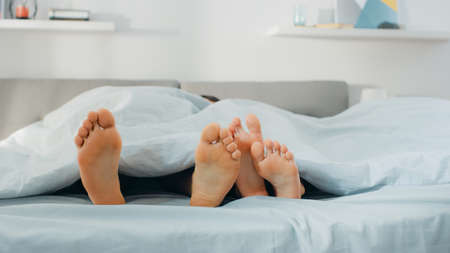 Cute Male and Female Lying in Bed with Feet Sticking from Under the Blanket, Touching, Flirting, Fooling Around. Bright and Cozy Bedroom. Standard-Bild