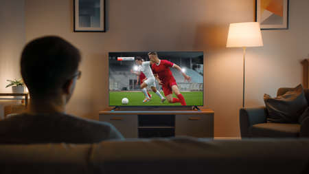 Young Man in Glasses is Sitting on a Sofa and Watching TV with a Soccer Match. Its Evening and Room at Home Has Working Lamps. Stock Photo