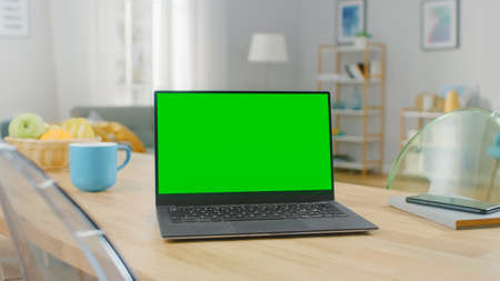 Shot of a Modern Laptop with a Horizontal Green Screen Mock Up on a Wooden Table at Home. Smartphone Lies on a Table Next to the Computer.