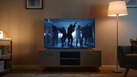 Shot of a TV with an Action Movie with Soldiers. Its Evening and Room at Home Has Working Lamps.