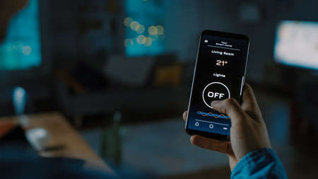 Close Up Shot of a Smartphone with Active Smart Home Application. Person is Tapping the Screen To Turn Lights On Off in the Room. Its Cozy Evening in the Apartment. Stock Photo
