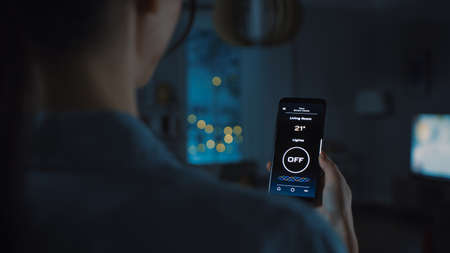 Young Beautiful Woman Gives a Voice Command to a Smart Home Application on Her Smartphone and Lights in the Room are Being Turned On. She Walks and Sits on a Couch. Its a Cozy Evening.