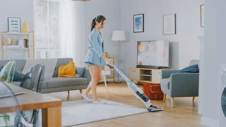Young Beautiful Woman in Jeans Shirt and Shorts is Vacuum Cleaning a Carpet in a Bright Cozy Room at Home. She Uses a Modern Cordless Vacuum. Shes Happy and Cheerful. Foto de archivo