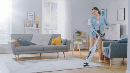 Young Beautiful Woman in Jeans Shirt and Shorts is Vacuum Cleaning a Carpet in a Bright Cozy Room at Home. She Uses a Modern Cordless Vacuum. Shes Happy and Cheerful. Banco de Imagens