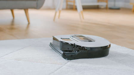 Close Up Shot of a Smart Robot Vacuum Cleaner Sucking Up Dust from a Carpet. Technological Home Appliance Device Moves Past Them.