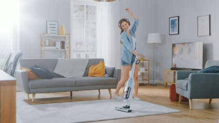 Young Beautiful Woman in Jeans Shirt and Shorts is Listening to Music on Her Headpones, Dancing and Vacuum Cleaning a Carpet in a Cozy Room at Home. She Uses a Cordless Vacuum. Shes Happy and Joyful. Banco de Imagens