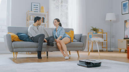 Smart Robot Vacuum Cleaner Sucking Up Dust from a Carpet. Beautiful Couple is Sitting on a Sofa and Talking in the Background. Technological Home Appliance Device Moves Past Them. Banque d'images