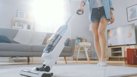 Close Up Shot of a Young Beautiful Woman in Jeans Shirt and Shorts Vacuum Cleaning a Carpet in a Bright Cozy Room at Home. She Uses a Modern Cordless Vacuum. Shes Happy and Cheerful. Archivio Fotografico
