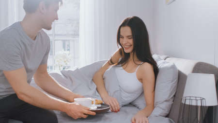 Shot of a Caring Young Man Bringing Tray with Breakfast in Bed to His Lovely Female Partner. Ideal Tender Relationship and Coffee and Croissants in Bed. Stock Photo