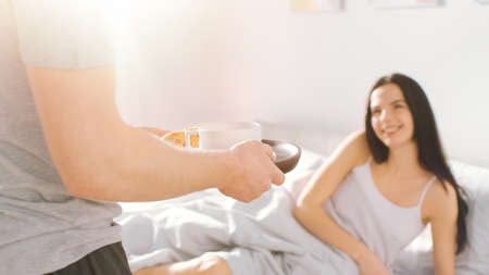 Shot of a Caring Young Man Bringing Tray with Breakfast in Bed to His Lovely Female Partner. Ideal Tender Relationship and Coffee and Croissants in Bed. Shot with Warm Sunlight.