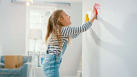 Happy Little Girl Dips Her Hands in Yellow and Red Paint and Starts Painting on the Wall. She is Having Fun and Laughs. Home is Being Renovated.