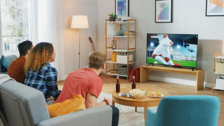 Three Sports Fans Sitting on a Couch in the Living Room Watch Important Soccer Match, Worry and Cheering For their Team. Bright Cozy Apartment with Friends Eating Snacks and Having Fun.